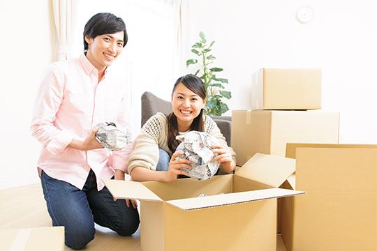 引越しの荷物を梱包するカップル